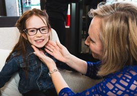 Happy young girl trying on eye glasses with optician