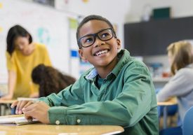 Child smiling in class with glasses